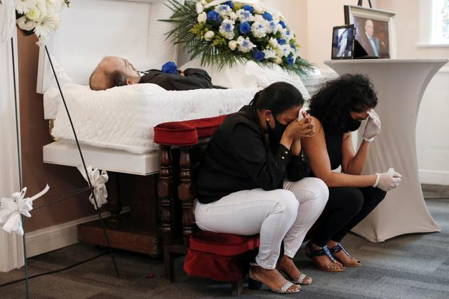 FILE PHOTO: The body of Jose Holguin, 50, originally from the Dominican Republic and who died of complications related to the coronavirus disease (COVID-19), is seen as his partner Maria Ortiz (C) and his sister Maria Holguin (C) sit beside him during his viewing service at International Funeral & Cremation Services in the Harlem neighborhood of Manhattan, New York City, U.S., May 16, 2020. REUTERS/Andrew Kelly