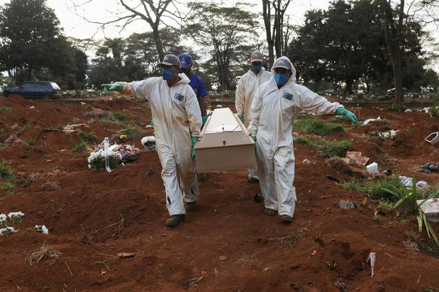 Gravediggers wearing protective suits carry the coffin of a person who died from the coronavirus disease (COVID-19) during a ceremony with no relatives, at Vila Formosa cemetery, Brazil's biggest cemetery, in Sao Paulo, Brazil, May 22, 2020. REUTERS/Amanda Perobelli