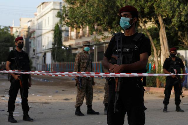 Police officers guard a cordoned-off street leading to the site of a passenger plane crash in a residential area near an airport in Karachi, Pakistan May 23, 2020. REUTERS/Akhtar Soomro