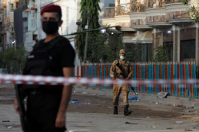 Army soldier walks along a cordoned-off street leading to the site of a passenger plane crash in a residential area near an airport in Karachi, Pakistan May 23, 2020. REUTERS/Akhtar Soomro