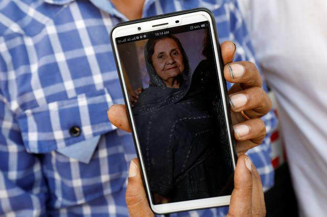 Shahid Ahmed, 45, holds his mobile phone displaying photo of his mother Irshad Begum, 72, who was killed in a plane crash, outside a morgue in Karachi, Pakistan May 23, 2020. REUTERS/Akhtar Soomro