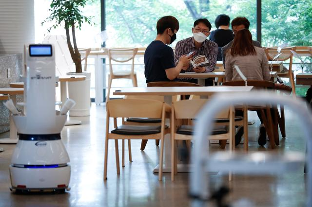 Customers wait at a cafe where a robot that takes orders, makes coffee and brings the drinks straight to customers is being used in Daejeon, South Korea, May 25, 2020. REUTERS/Kim Hong-Ji