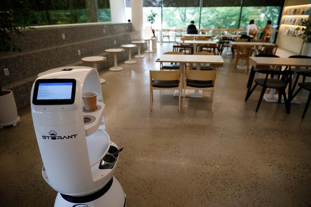 A robot that takes orders, makes coffee and brings the drinks straight to customers at their seats is seen at a cafe in Daejeon, South Korea, May 25, 2020. REUTERS/Kim Hong-Ji