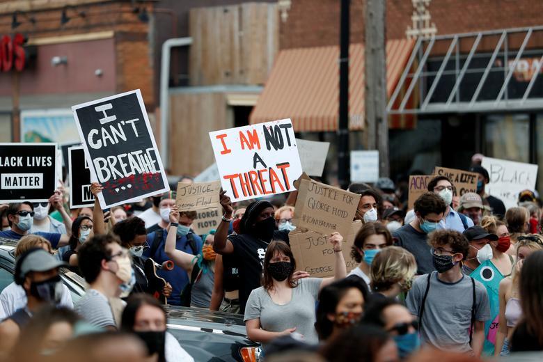 """Protestocular, George Floyd'un 26 Mayıs Minneapolis'te boynunda diz çökmüş bir polis memuru tarafından tutuklandığı sahnede toplandı. Dört Minneapolis polis memuru, Salı günü bakan bir videoda görülen silahsız siyah adamın ölümü üzerine kovuldu Sokakta hava soluyor ve inliyor, """"Nefes alamıyorum"""", beyaz bir subay boynunda birkaç dakika diz çöküyor.  REUTERS / Eric Miller"""