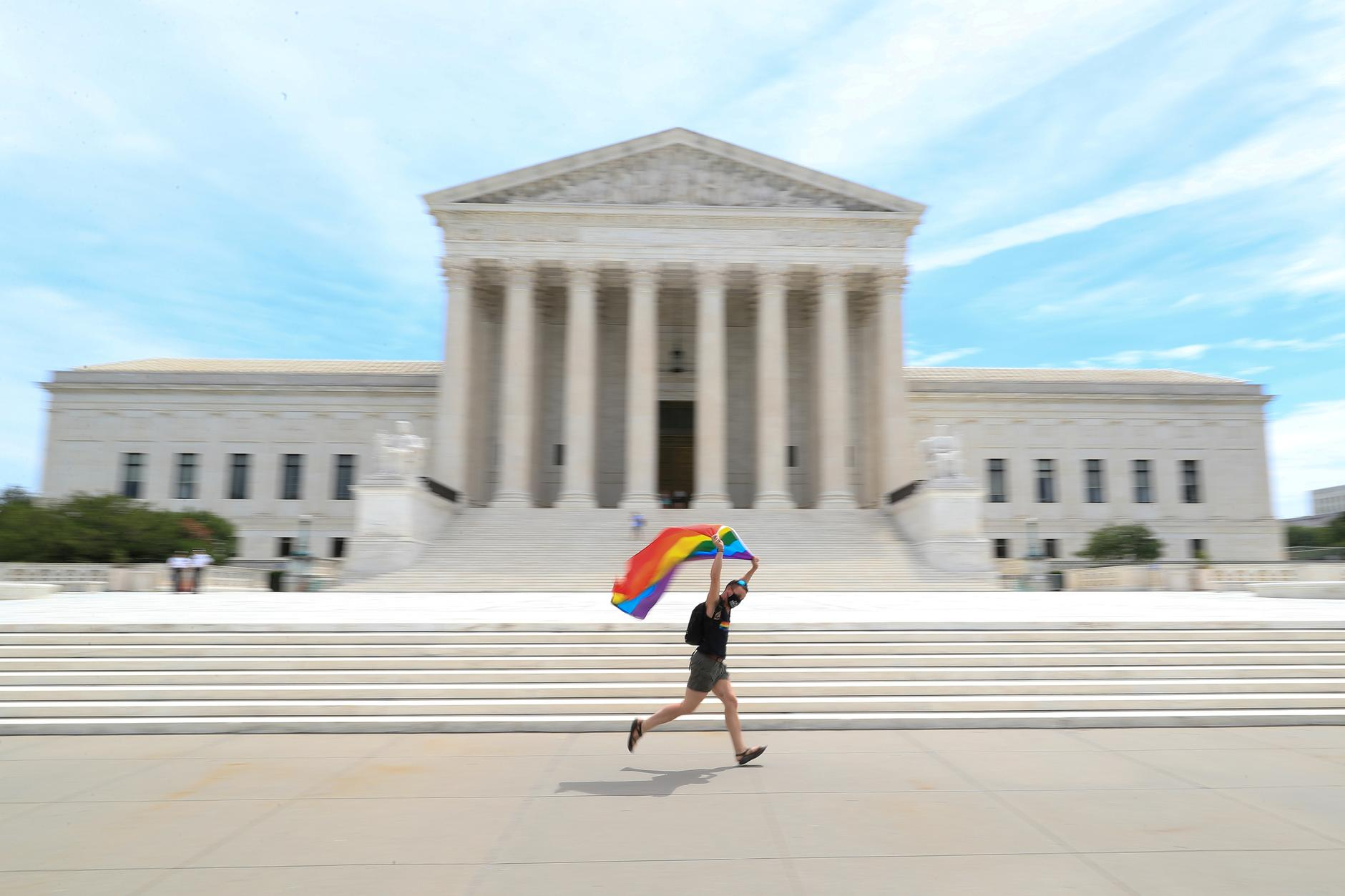 Joseph Fons holding a Pride Flag, runs in front of the U.S. Supreme Court building after the court ruled that a federal law banning workplace discrimination also covers sexual orientation, in Washington, D.C., U.S., June 15, 2020. REUTERS/Tom Brenner