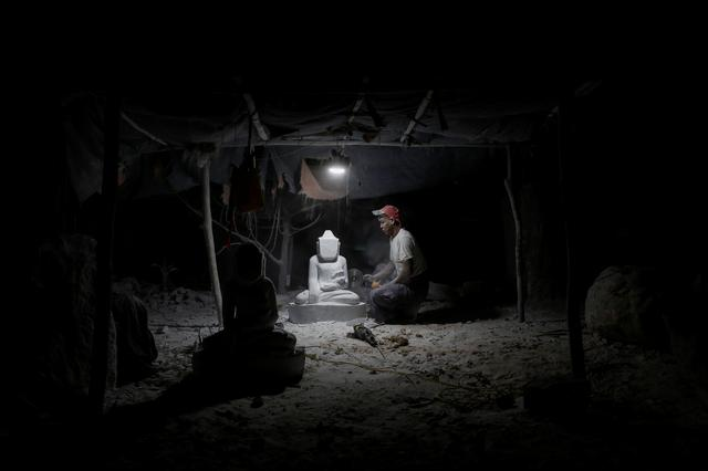 A marble carver works on a statue of a Buddha in his carving workshop in Sagyin village, Mandalay, Myanmar. For generations, artisans in this part of Buddhist-majority Myanmar have carved out a living from white marble, fashioning mostly colossal Buddha statues to be sold in the nearby city of Mandalay or exported to neighboring China and Thailand. Picture taken February 13, 2019. REUTERS/Ann Wang