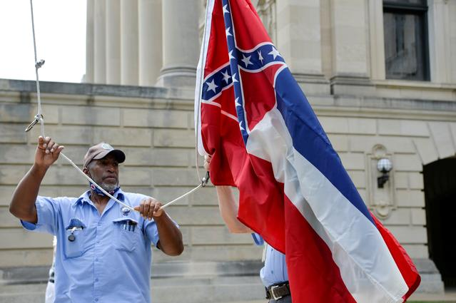 Willie Townsend, an employee of the Mississippi State Capitol, raises and lowers commemorative state flags that are purchased by people from all around the world after being flown at the Capitol, hours before Mississippi Governor Tate Reeves signed a bill into law replacing the current state flag that includes a Confederate emblem, in Jackson, Mississippi, June 30, 2020. The removal of the flag, a long-simmering source of controversy in one of the breakaway Southern states that fought in the 1860s American Civil War, follows the death of George Floyd. REUTERS/Suzi Altman