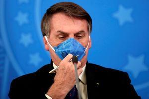 FILE PHOTO: Brazil's President Jair Bolsonaro adjusts his protective face...