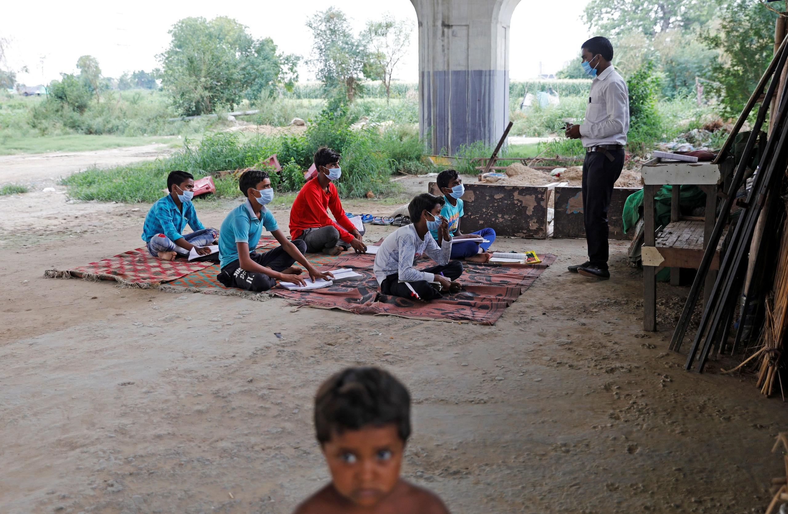 Satyendra Pal, a college student, conducts an open-air class for the students of 9th class from a slum area, who do not have access to internet facilities and miss their online lessons, after authorities closed all the schools in March following the outbreak of the coronavirus disease (COVID-19), in New Delhi, India, July 8, 2020. REUTERS/Adnan Abidi