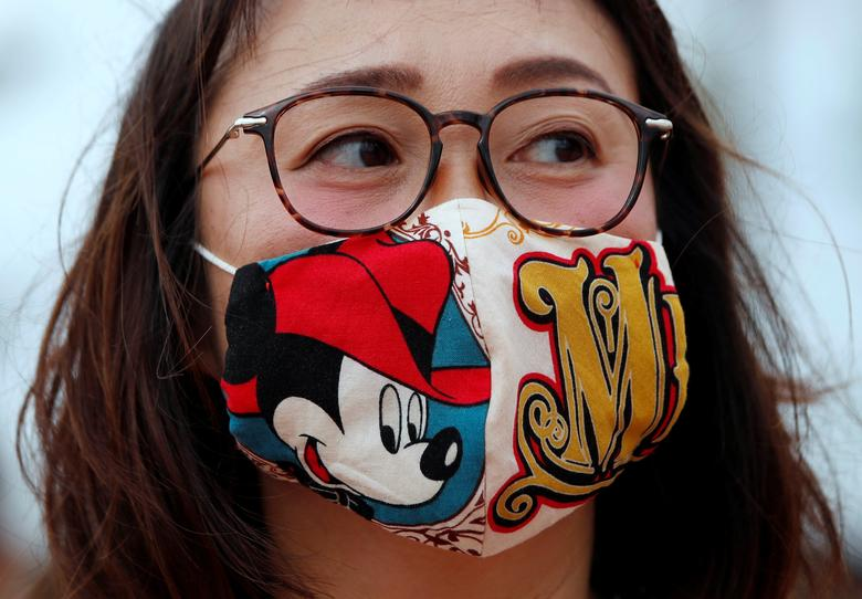 A visitor wearing a handmade Mickey Mouse mask waits for the reopening of Tokyo Disneyland along with Tokyo DisneySea at the entrance gate of Tokyo Disneyland in Urayasu, east of Tokyo, Japan July 1, <span dir=