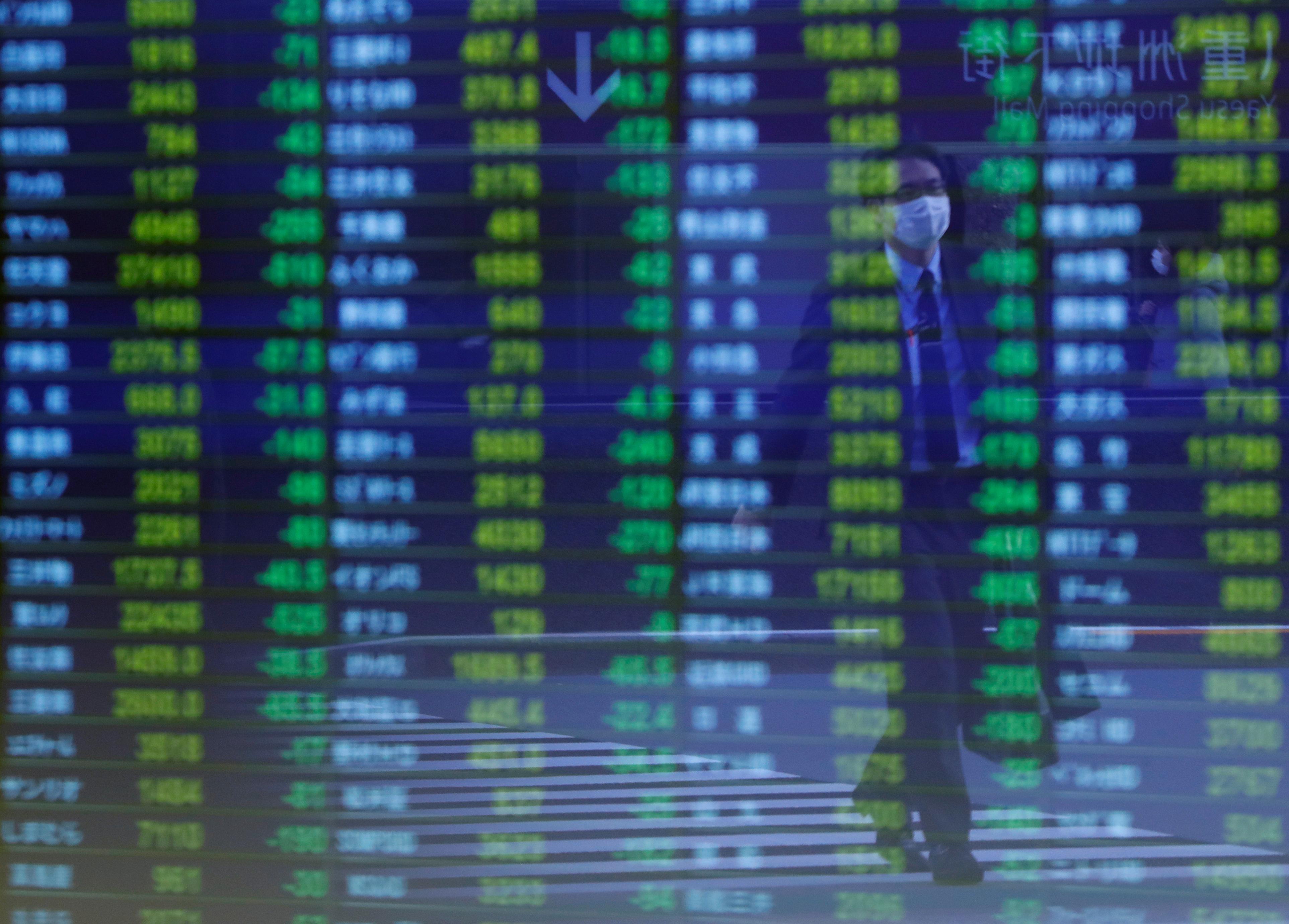 A man wearing protective face mask, following an outbreak of the coronavirus, is reflected on a screen displaying stock prices outside a brokerage in Tokyo, Japan March 6, 2020.   Issei Kato