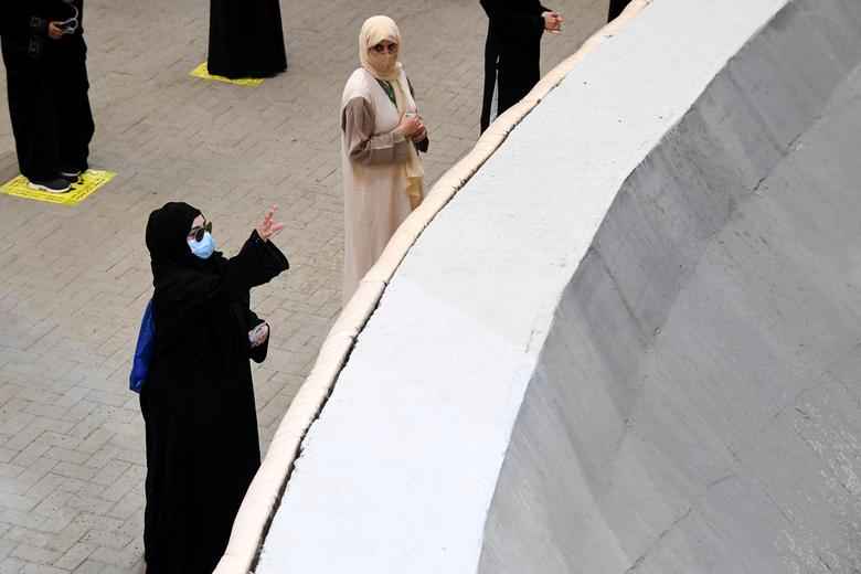 Muslim pilgrims, wearing face masks, cast stones at pillars symbolizing Satan during the annual Haj pilgrimage in Mina, near the holy city of Mecca, Saudi Arabia July 31, <span dir=