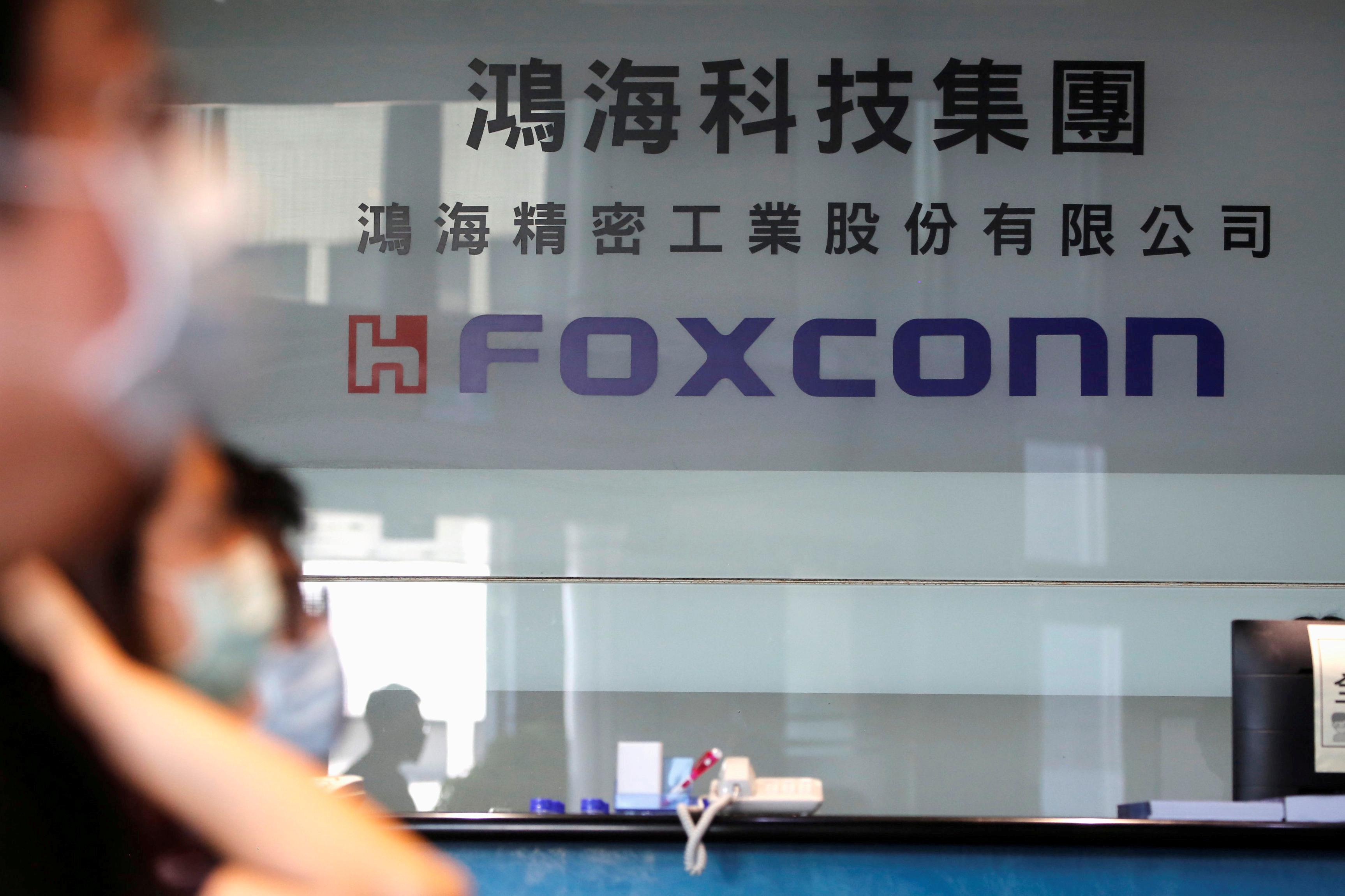 People wear masks to protect themselves from coronavirus disease (COVID-19), while listening to the annual general meeting at the lobby of Foxconn
