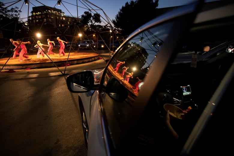 """People sit inside their cars and watch an open-air performance of """"Birth of the Phoenix"""" by Vertigo Dance Company at the parking lot of Jerusalem's Old Station amid the coronavirus crisis, in Jerusalem August 4, 2020. REUTERS/Ronen Zvulun"""