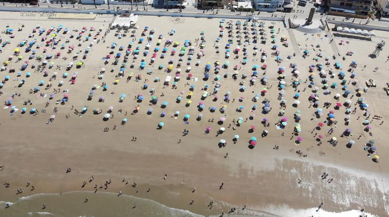 People practice social distancing as they visit a beach during the coronavirus outbreak, in Chipiona, Spain July 25, 2020. Facebook/Local police Chipiona-092 via REUTERS