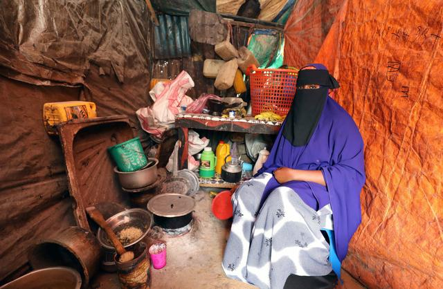 Hafsa Ali Osman, 15, a Somali girl suspected of being forced into marriage as a child cooks inside her makeshift shelter at the Alafuuto camp for internally displaced persons in Garasbaaley district of Mogadishu, Somalia August 14, 2020. Picture taken August 14, 2020. REUTERS/Feisal Omar