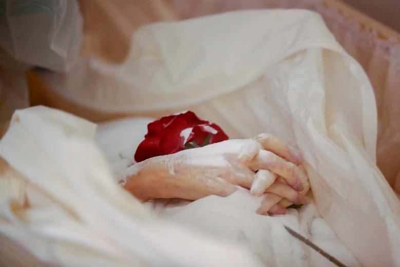 A rose sits between the hands of a person who died of the coronavirus at a mortuary in Brussels, Belgium, April 9. REUTERS/Yves Herman