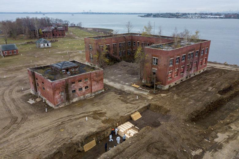 Bodies are buried on New York's Hart Island amid the coronavirus outbreak in New York City, April 9. The city has used Hart Island to bury New Yorkers with no known next of kin or whose family are unable to arrange a funeral since the 19th century. Officials hired contract laborers to bury the dead in its potter's field as the city's daily death rate reached grim new records. REUTERS/Lucas Jackson