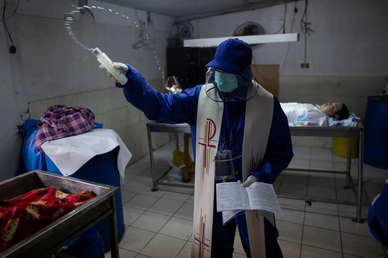 Filipino Catholic priest Rey Amancio, 31, wears his personal protective equipment as he blesses a deceased person inside a morgue, amid the prohibition of religious gatherings, including funerals, during the government-imposed lockdown in Caloocan, Metro Manila, Philippines, April 20. REUTERS/Eloisa Lopez