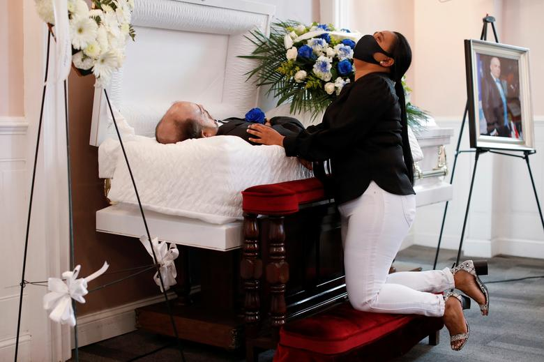 Maria Ortiz reacts while kneeling beside the body of her partner Jose Holguin, 50, originally from the Dominican Republic and who died of complications related to the coronavirus, during a viewing service for Holguin at International Funeral & Cremation Services in Harlem, New York, May 16. REUTERS/Andrew Kelly