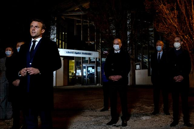 French President Emmanuel Macron, flanked by French Interior Minister Gerald Darmanin and French Education Minister Jean-Michel Blanquer, speaks to the press following a stabbing attack in the Conflans-Sainte-Honorine suburb of Paris, France, October 16, 2020. Abdulmonam Eassa/Pool via REUTERS