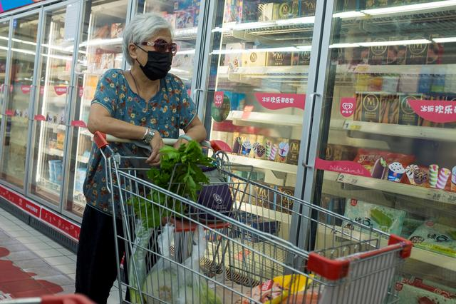 FILE PHOTO: A woman looks at frozen food products in a supermarket in Beijing, China, August 13, 2020. REUTERS/Thomas Peter