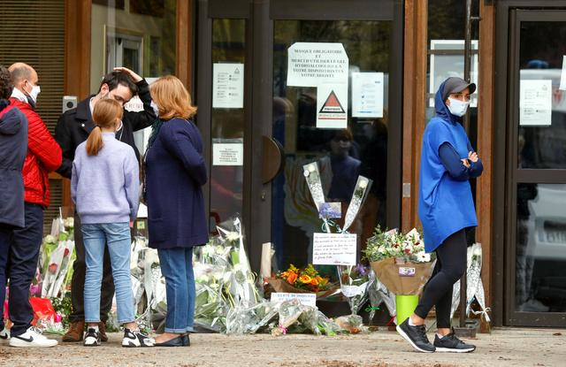 People bring flowers to the Bois d'Aulne college after the attack in the Paris suburb of Conflans St Honorine, France, October 17, 2020. REUTERS/Charles Platiau