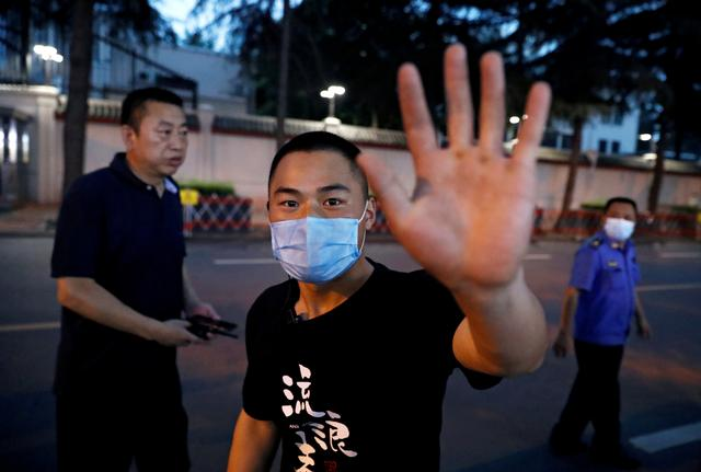 FILE PHOTO: A plain clothes police officer gestures as he approaches the photographer taking pictures of the U.S. Consulate General in Chengdu, Sichuan province, China July 24, 2020. REUTERS/Thomas Peter/File Photo