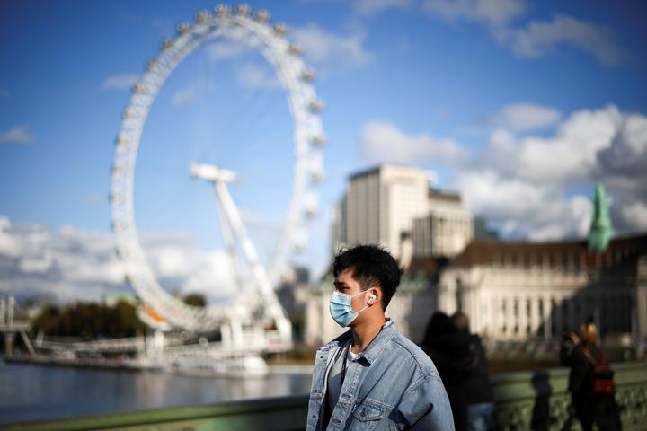 A man wearing a protective face mask walks across Westminster bridge,...