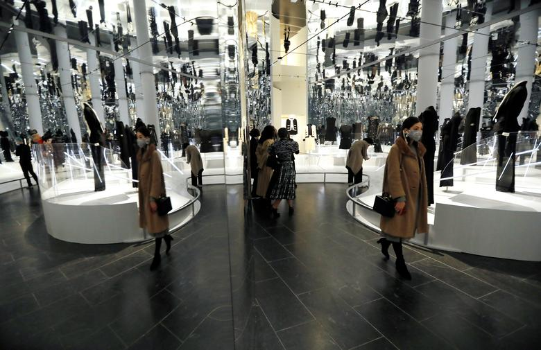 """Visitors are reflected in mirrors amid creations displayed at The Costume Institute's upcoming exhibition """"About Time: Fashion and Duration"""" during a press preview at the Metropolitan Museum of Art in Manhattan, New York, October 26, 2020. REUTERS/Mike Segar"""