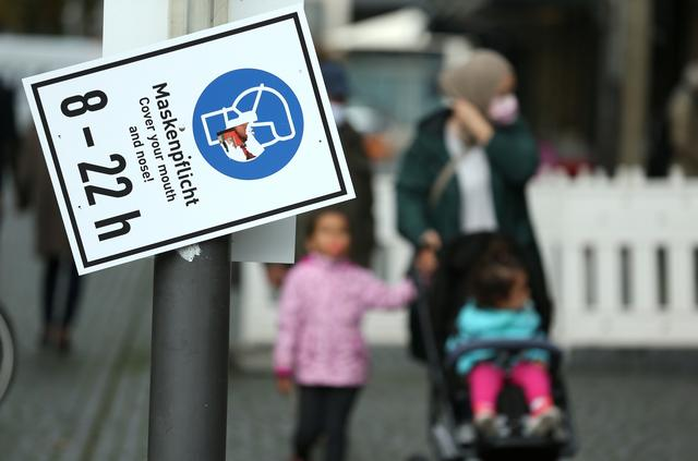 Pedestrians walk along a sign that reminds to wear a face mask as the coronavirus disease (COVID-19) outbreak continues in Frankfurt, Germany October 29, 2020. REUTERS/Ralph Orlowski