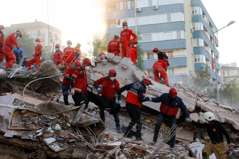 Ege Denizi'nde meydana gelen depremin ardından bir şantiyede kurtarma operasyonları gerçekleştirildiği için işçiler bir kurbanın cesedini taşıyorlar, Türkiye'nin kıyı ili İzmir'de, 1 Kasım 2020. REUTERS / Kemal Aslan