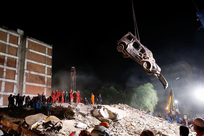 Ege Denizi'nde Ege Denizi'nde meydana gelen depremin ardından emniyete alınan bir sahada kurtarma operasyonu gerçekleştirildiği için aracı kaldıran vinç, 1 Kasım 2020. REUTERS / Kemal Aslan
