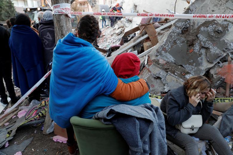Ege Denizi'nde meydana gelen depremden etkilenen yakınları, İzmir'in kıyı ilinde kurtarma operasyonlarını izlerken enkazın üzerinde duruyor, 31 Ekim 2020. REUTERS / Murad Sezer