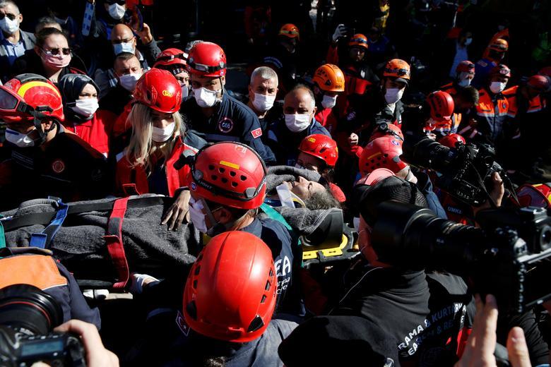 Kurtarma ekipleri, 31 Ekim'de Türkiye'nin Ege liman kenti İzmir'de meydana gelen depremden sağ kalan birini yıkılan binadan dışarı taşıyorlar. REUTERS / Kemal Aslan & nbsp;