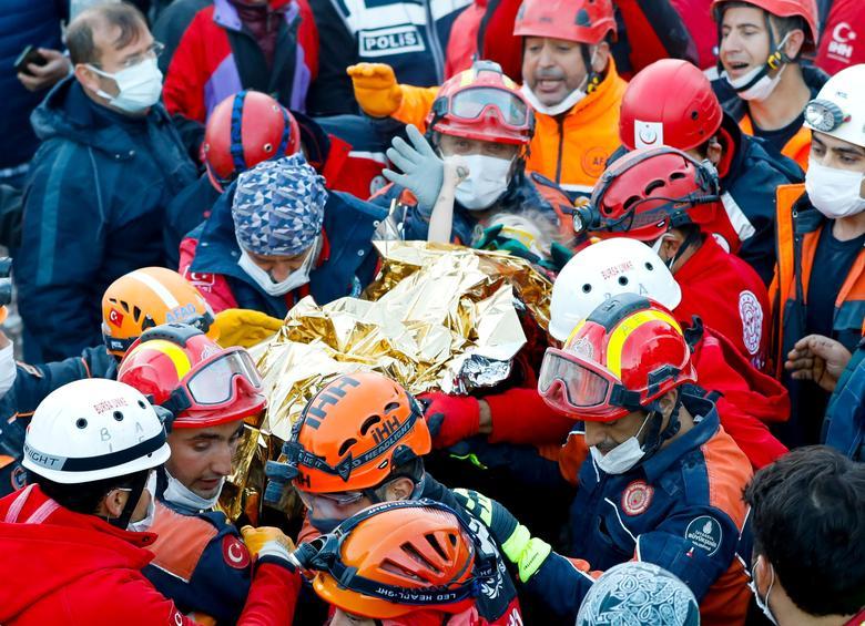 Hayatta kalan üç yaşındaki Elif Perinçek, Türkiye'nin Ege liman kenti İzmir'de meydana gelen depremden sonra çöken bir binada kurtarma görevlisinin baş parmağını tutuyor, 2 Kasım Serkan Oktar / İstanbul İtfaiyesi