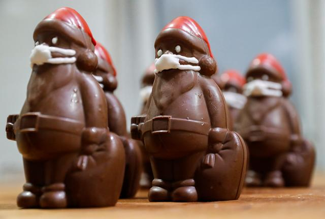 Chocolate Santas wearing protective face masks are seen in the workshop of the Hungarian confectioner Laszlo Rimoczi, during the coronavirus disease (COVID-19) outbreak in Lajosmizse, Hungary, November 20, 2020. REUTERS/Bernadett Szabo