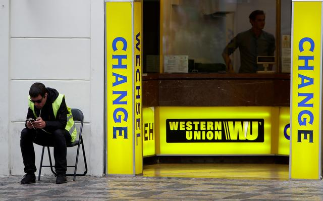 FILE PHOTO: A man sits on a chair next to Western Union currency exchange office in Prague, Czech Republic, September 8, 2017.   REUTERS/David W Cerny/File Photo