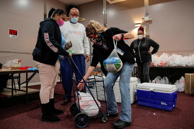 FILE PHOTO: Volunteers hand out Thanksgiving turkeys and bags of free holiday food to those in need at the Central Family Life Center, as the global outbreak of the coronavirus disease (COVID-19) continues, in Staten Island, New York, U.S., November 19, 2020.  REUTERS/Brendan McDermid/File Photo