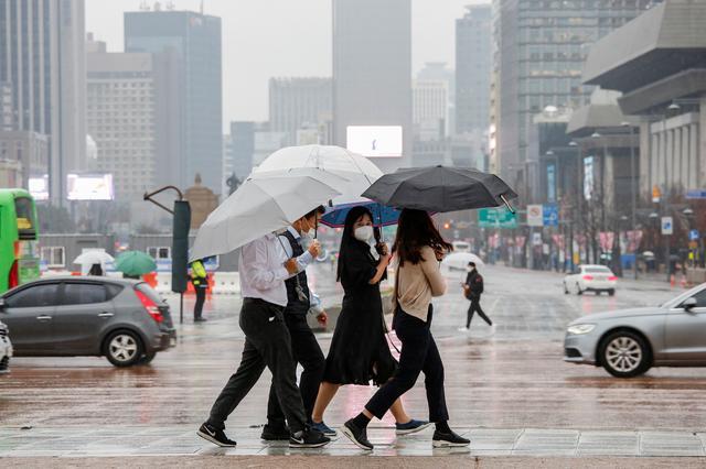FILE PHOTO: Pedestrians wearing masks walk with umbrellas as it rains amid the coronavirus disease (COVID-19) pandemic in central Seoul, South Korea, November 19, 2020.    REUTERS/Heo Ran