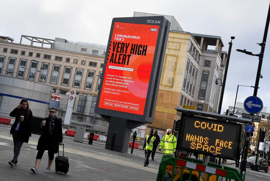 Pedestrians walk past a British government health information advertisement highlighting new restrictions amid the spread of the coronavirus disease (COVID-19), London, Britain, December 19, 2020. REUTERS/Toby Melville