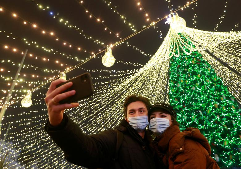A couple wearing protective masks against COVID-19 take a selfie in a front of Christmas tree in central Kyiv, Ukraine December 20, 2020. REUTERS/Valentyn Ogirenko