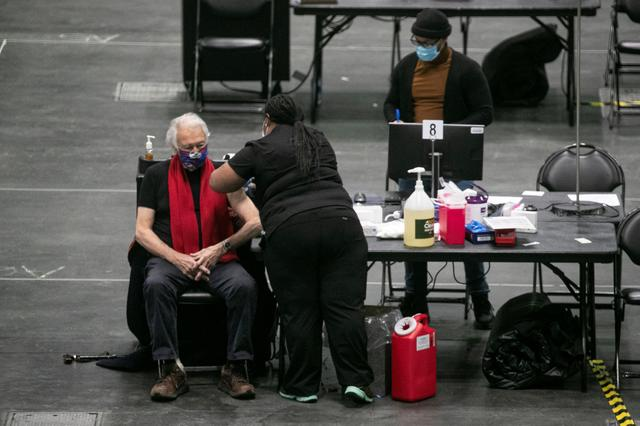 A man receives a dose of the coronavirus disease (COVID-19) vaccine at the New York State COVID-19 vaccination site at the Jacob K. Javits Convention Center, in New York City, U.S., January 13, 2021.  REUTERS/Brendan McDermid