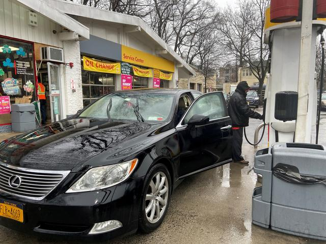 FILE PHOTO: Julio Barrios attends to a customer at a gas station in Scarsdale, New York, U.S., March 13, 2020. REUTERS/Jessica Resnick-Ault/File Photo