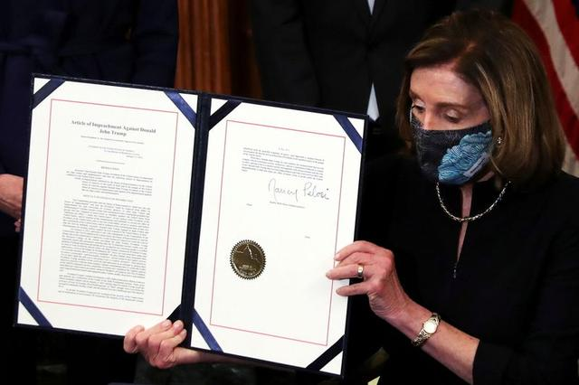 U.S. House Speaker Nancy Pelosi (D-CA) shows the article of impeachment against U.S. President Donald Trump after signing it in an engrossment ceremony, at the U.S. Capitol in Washington January 13, 2021. REUTERS/Leah Millis
