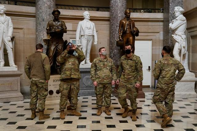 National Guard members walk and take pictures as Democrats debate one article of impeachment against U.S. President Donald Trump at the U.S. Capitol, in Washington, U.S., January 13, 2021. REUTERS/Joshua Roberts