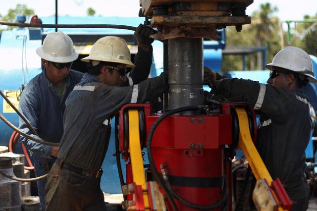 FILE PHOTO: Oil field technicians work with a drill at a rig of Ecuador's state oil company Petroamazonas, in Tiputini, Ecuador October 19, 2017. REUTERS/Daniel Tapia