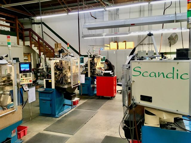 An operator programs a CNC wireforming machine to make a custom spring at Scandic Springs' factory in San Leandro, California, U.S. February 17, 2021. Scandic Springs Inc/Handout via REUTERS