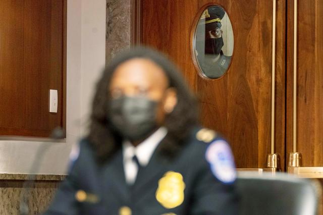 An officer looks through a window as Capitol Police Capt. Carneysha Mendoza, foreground, prepares to speak at a Senate Homeland Security and Governmental Affairs & Senate Rules and Administration joint hearing on Capitol Hill, Washington, U.S., February 23, 2021, to examine the January 6th attack on the Capitol. Andrew Harnik/Pool via REUTERS