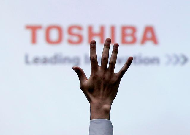 FILE PHOTO: A reporter raises his hand for a question during a Toshiba news conference at the company headquarters in Tokyo, Japan June 23, 2017.  REUTERS/Issei Kato